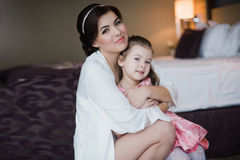 Beautiful mother hugs daughter in the bedroom Royalty Free Stock Images