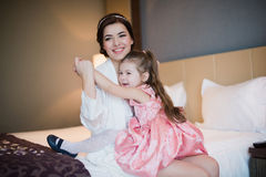 Beautiful mother hugs daughter in the bedroom Royalty Free Stock Image