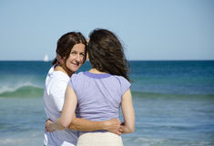 Beautiful mother hugs daughter at tropical beach Stock Photos