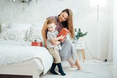 Beautiful mother hugs her son on the couch royalty free stock photo