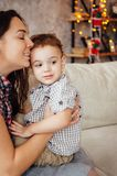 Beautiful mother hugs her son on the couch near the xmas tree royalty free stock photo