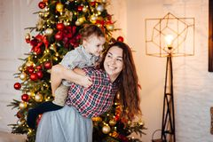 Beautiful mother hugs her son on the couch near the xmas tree stock images