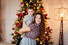 Beautiful mother hugs her son on the couch near the xmas tree stock photography