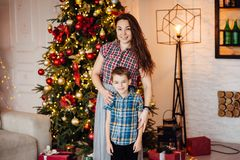 Beautiful mother hugs her son on the couch near the xmas tree stock photos