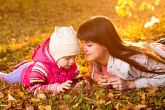 Beautiful mother and kid girl laying on autumnal leaves outdoors Royalty Free Stock Photography