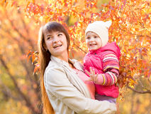 beautiful mother with kid girl outdoor in autumnal park Stock Photos