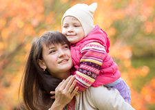 Beautiful mother with kid girl outdoors in fall Stock Photos