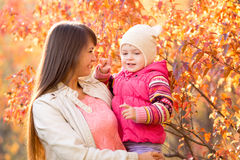 Beautiful mother with kid girl outdoors in fall Royalty Free Stock Photo