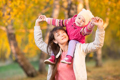 Beautiful mother with kid girl walking outdoors in autumnal park Royalty Free Stock Photo