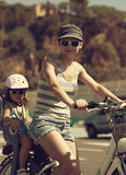 Beautiful mother and kid riding on bicycle outdoors Royalty Free Stock Photo