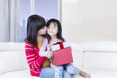 Beautiful mother kisses her child on sofa Stock Image