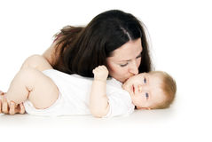 Beautiful mother kissing baby on the cheek Stock Photos