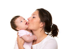 Beautiful mother kissing baby girl hug on white. Background Stock Photo