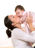 Beautiful mother kissing baby girl hug on white Stock Images