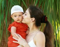 Beautiful mother kissing fun baby stock images