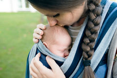 Beautiful mother kissing her son in sling, green nature. Beautiful young mother kissing her newborn baby son in sling outside in green nature Royalty Free Stock Image