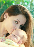 Beautiful mother kissing newborn baby Stock Photography