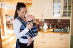 Beautiful mother in kitchen with her son sleeping in sling Royalty Free Stock Images