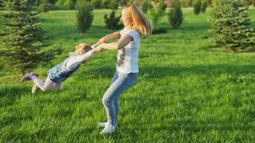 Beautiful mother lifts girl and begins turning her around stock footage