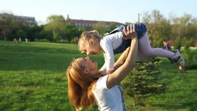 Beautiful mother lifts high her cheerful girl and laughing stock video footage