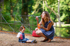 Beautiful mother and little daughter blowing soap bubbles in sum Royalty Free Stock Photos
