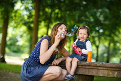 Beautiful mother and little daughter blowing soap bubbles in sum Royalty Free Stock Image