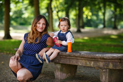 Beautiful mother and little daughter blowing soap bubbles in sum Stock Image