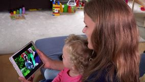Beautiful mother with little daughter girl watch family movie on tablet screen. stock video footage
