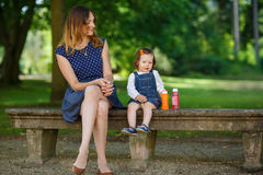 Beautiful mother and little daughter walking in summer park Royalty Free Stock Photo