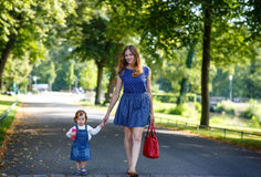 Beautiful mother and little daughter walking in summer park Royalty Free Stock Photos