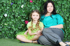 Beautiful mother and little girl sit on grass in garden Stock Photo
