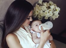 Beautiful mother with luxurious dark hair and her little baby Stock Photos