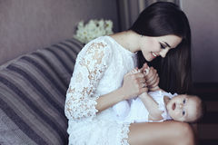 Beautiful mother with luxurious dark hair and her little baby Stock Image