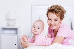 Beautiful mother lying with her baby on the bed Stock Image