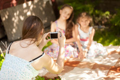 Beautiful mother making photo of daughters on picnic Stock Image