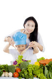 Beautiful mother making a salad with her son. Portrait of beautiful mother smiling at the camera while making a salad with her son, isolated on white background Royalty Free Stock Photos