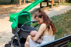 Mother and child breastfeeding outside scene, woman caring baby in loving arms and feeding with her breast milk. Beautiful mother on maternity leave holding and stock photo