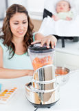 Beautiful mother mixing carrot with a blender Stock Images