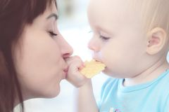 Beautiful mother playing with her beautiful child , the child eats the cookie and laughs stock images
