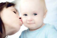 Beautiful mother playing with her beautiful child , the child eats the cookie and laughs royalty free stock photos