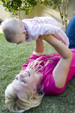 Beautiful mother playing with her newborn baby Stock Photos