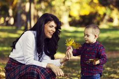 Beautiful  mother plays with her son in the park in autumn Royalty Free Stock Photography