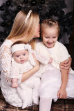Beautiful mother posing with her cute daughters posing beside Christmas tree Stock Photography