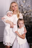 Beautiful mother posing with her cute daughters posing beside Christmas tree Royalty Free Stock Photo