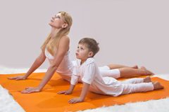A beautiful  mother practices yoga with her son Royalty Free Stock Images