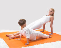 A beautiful  mother practices yoga with her son Stock Image