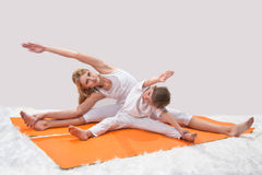 A beautiful  mother practices yoga with her son Stock Photography
