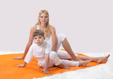 A beautiful  mother practices yoga with her son Stock Images