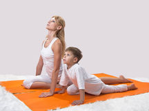 A beautiful  mother practices yoga with her son Stock Photo