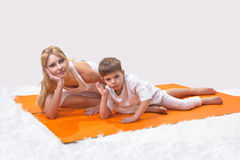A beautiful  mother practices yoga with her son Stock Photos